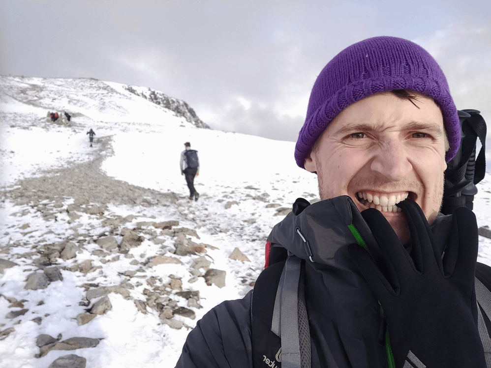 man on a hiking winter trip with a purple cap