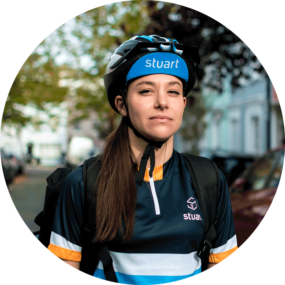 Female Stuart courier wearing helmet for safety stands on a leafy London street