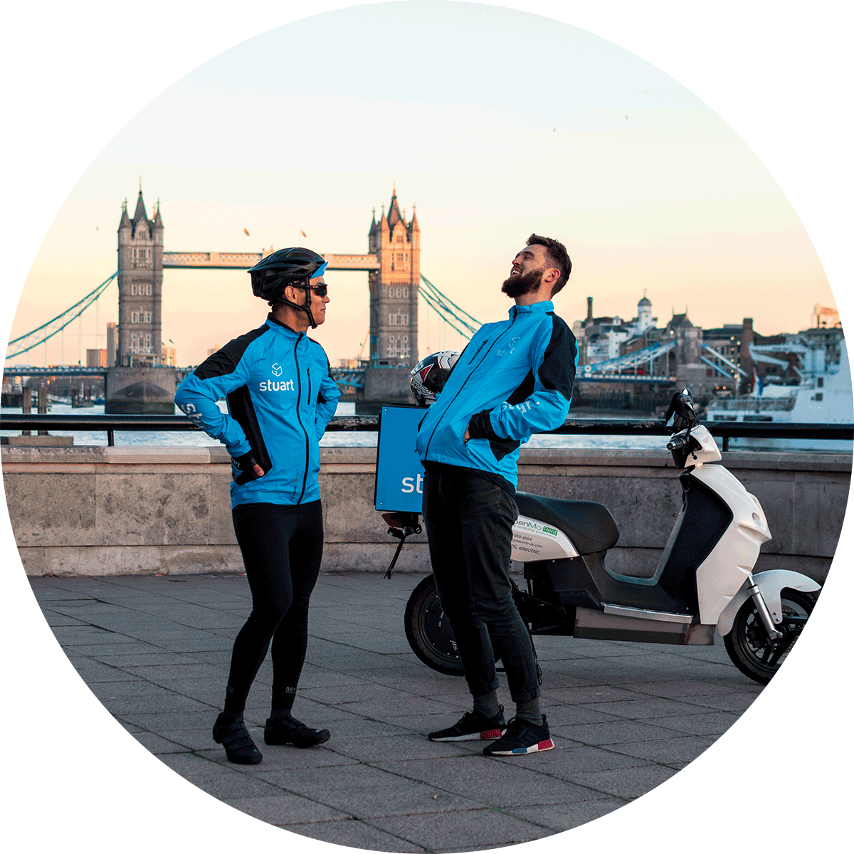 Two male Stuart couriers laughing, Tower Bridge in London is in the background.
