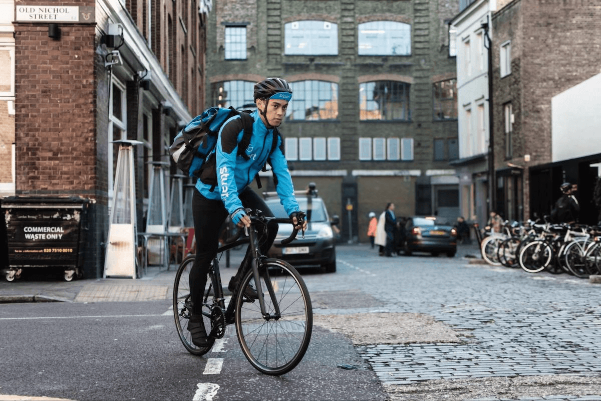 Courier cycling on a cobbled street
