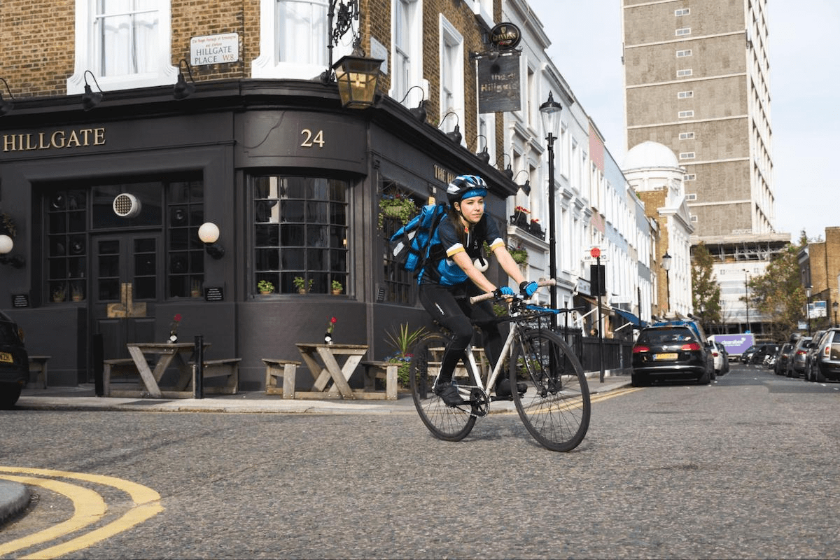 Courier cycling on a London street